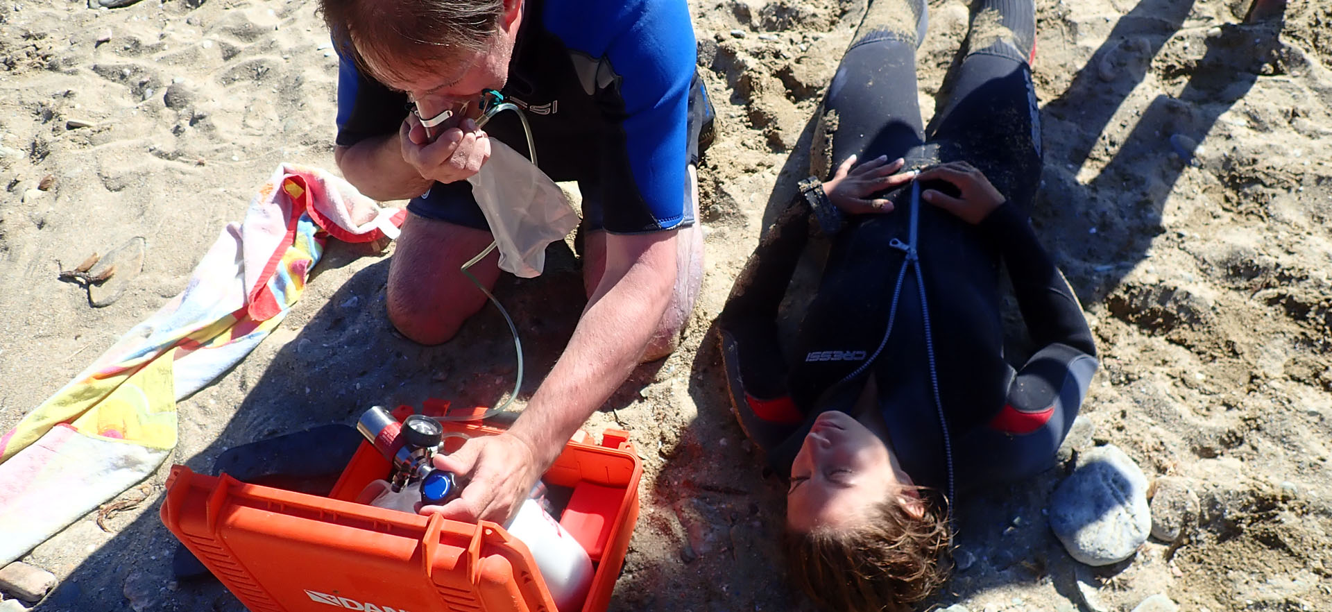 Divers practising first aid on a beach